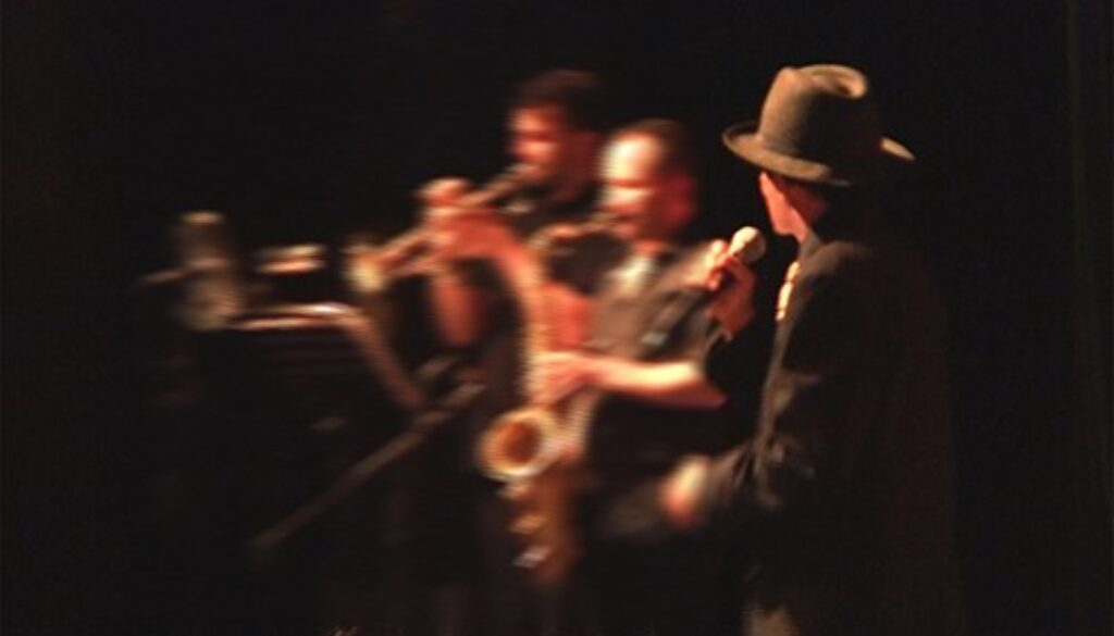 gregory abbott on stage with horns